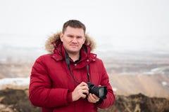 Homme d'une cinquantaine d'années avec un appareil-photo dans le voyage photo stock