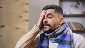Homme d'une cinquantaine d'années ayant le mal de tête et la fièvre terribles, se sentant malade ou hungover banque de vidéos