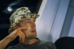 Homme d'une cinquantaine d'années dans un chapeau montant un train la nuit pensant environ images libres de droits
