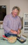 Homme d'une cinquantaine d'années administrant le mélange à la cuillère de gâteau de fruit dans a Image libre de droits
