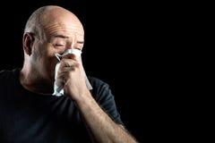Homme d'une cinquantaine d'années avec la grippe soufflant son nez photographie stock