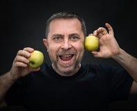 Homme d'une cinquantaine d'années avec pommes vertes Photos stock