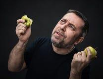 Homme d'une cinquantaine d'années avec pommes vertes Images stock