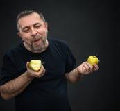 Homme d'une cinquantaine d'années avec pommes vertes Image stock