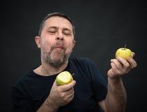 Homme d'une cinquantaine d'années avec pommes vertes Photographie stock