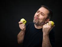 Homme d'une cinquantaine d'années avec pommes vertes Photo stock