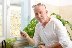 Homme d'une cinquantaine d'années avec un téléphone portable Photos libres de droits
