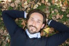 Homme d'une cinquantaine d'années bel se trouvant sur les feuilles d'automne en parc Photos libres de droits
