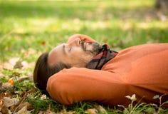 Homme d'une cinquantaine d'années bel se trouvant sur les feuilles d'automne en parc Photo libre de droits