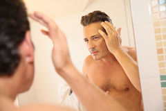 Homme d'une cinquantaine d'années dans le mirroro s'inquiétant de sa perte des cheveux photo libre de droits