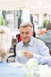 Homme d'une cinquantaine d'années de sourire ayant le café avec la femme au café de trottoir Photos stock