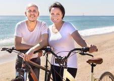 Homme d'une cinquantaine d'années et femme avec des bicyclettes marchant sur la plage image libre de droits