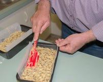 Homme d'une cinquantaine d'années lissant le mélange de gâteau avec Spatul Photographie stock libre de droits