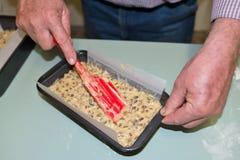 Homme d'une cinquantaine d'années lissant le mélange de gâteau de fruit avec la spatule Images libres de droits
