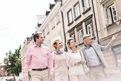 Homme d'une cinquantaine d'années montrant quelque chose aux amis tout en marchant dans la ville Photos libres de droits