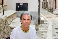 Homme d'une cinquantaine d'années s'asseyant dans des allées médiévales de ville Photos libres de droits