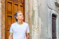 Homme d'une cinquantaine d'années visitant les allées médiévales de ville Image stock