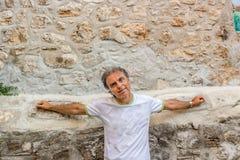 Homme d'une cinquantaine d'années visitant les allées médiévales de ville Images stock