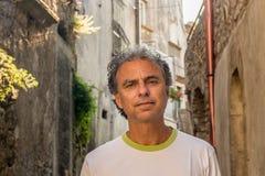 Homme d'une cinquantaine d'années visitant les allées médiévales de ville Photographie stock libre de droits