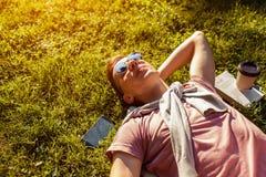 Homme d'université bel refroidissant au printemps le parc de campus Étudiant heureux de type se trouvant sur l'herbe avec son tél photo libre de droits
