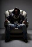 Homme dangereux s'asseyant dans le blanc Photos stock