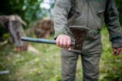 Homme dangereux tenant un acier fait sur commande, hache pointue Image stock