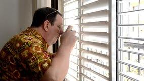 Homme dans aloha le tir de chemise par les jalousies en plastique banque de vidéos