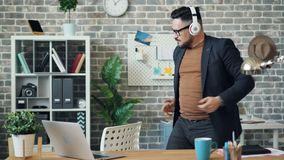 Homme dans des écouteurs dansant dans le bureau écoutant la musique appréciant la pause clips vidéos