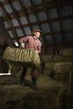 Homme dans des balles mobiles de grange de foin Images libres de droits