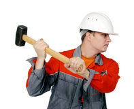 Homme dans des combinaisons avec un marteau dans des ses mains Image libre de droits