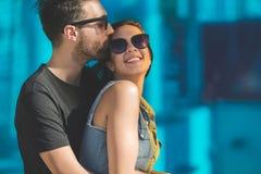 Homme dans des lunettes de soleil embrassant et embrassant l'amie heureuse Photos stock