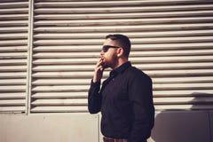 Homme dans des lunettes de soleil fumant une cigarette Photo libre de droits
