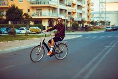 Homme dans des lunettes de soleil montant un vélo sur la rue de ville Images stock