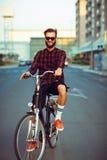 Homme dans des lunettes de soleil montant un vélo sur la rue de ville Image stock