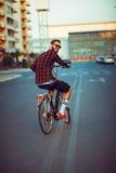Homme dans des lunettes de soleil montant un vélo sur la rue de ville Photos libres de droits