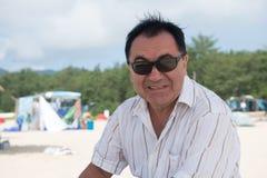 Homme dans des lunettes de soleil sur la plage Images stock