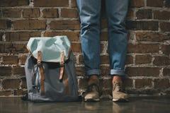 Homme dans des pantalons et des espadrilles de denim se tenant avec le sac à dos près du mur de briques Photo stock