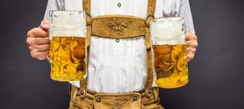 Homme dans des vêtements bavarois traditionnels tenant la tasse de bière images stock