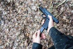 Homme dans des v?tements militaires chargeant une arme ? feu photos libres de droits