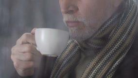 Homme dans l'écharpe sur son cou buvant du thé chaud regardant le froid et la grippe pluvieux de temps clips vidéos