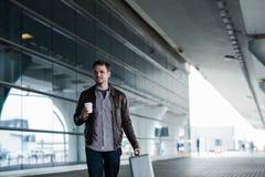 Homme dans l'aéroport tenant un sac et marchant avec la tasse de café Photos stock
