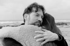 Homme dans l'amour étreignant l'épouse forte devant l'océan noir et blanc Photographie stock libre de droits