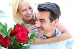 Homme dans l'amour donnant les roses rouges à l'épouse Images stock
