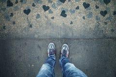 Homme dans l'amour se tenant sur le plancher grunge bleu d'asphalte de coeur Photographie stock libre de droits