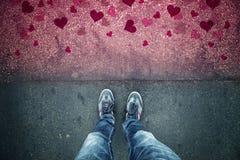 Homme dans l'amour se tenant sur le plancher grunge rouge d'asphalte de coeur Photo libre de droits