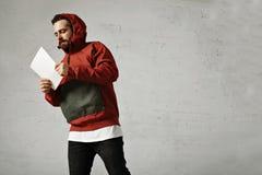 Homme dans l'anorak rouge avec la feuille de papier blanche photographie stock libre de droits