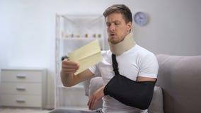 Homme dans l'enveloppe cervicale d'ouverture de bride de collier et de bras de mousse avec la facture, prix élevé banque de vidéos