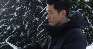 Homme dans l'habillement chaud utilisant le comprimé numérique 4k banque de vidéos