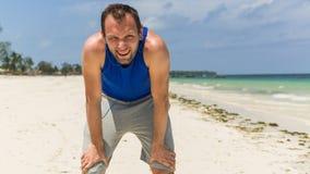Homme dans l'habillement de sport se reposant après exercice sur la plage. Photographie stock