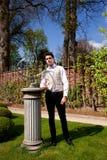Homme dans l'habillement, le pilier et le cadran solaire de Vicorian en parc Photographie stock